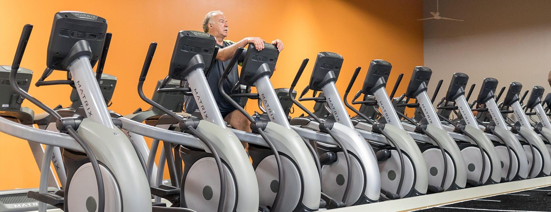 man using cardio machine in spacious modern gym