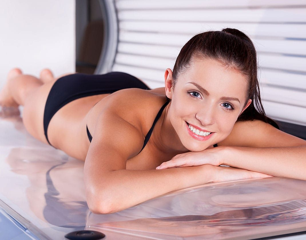 smiling woman laying on tanning bed