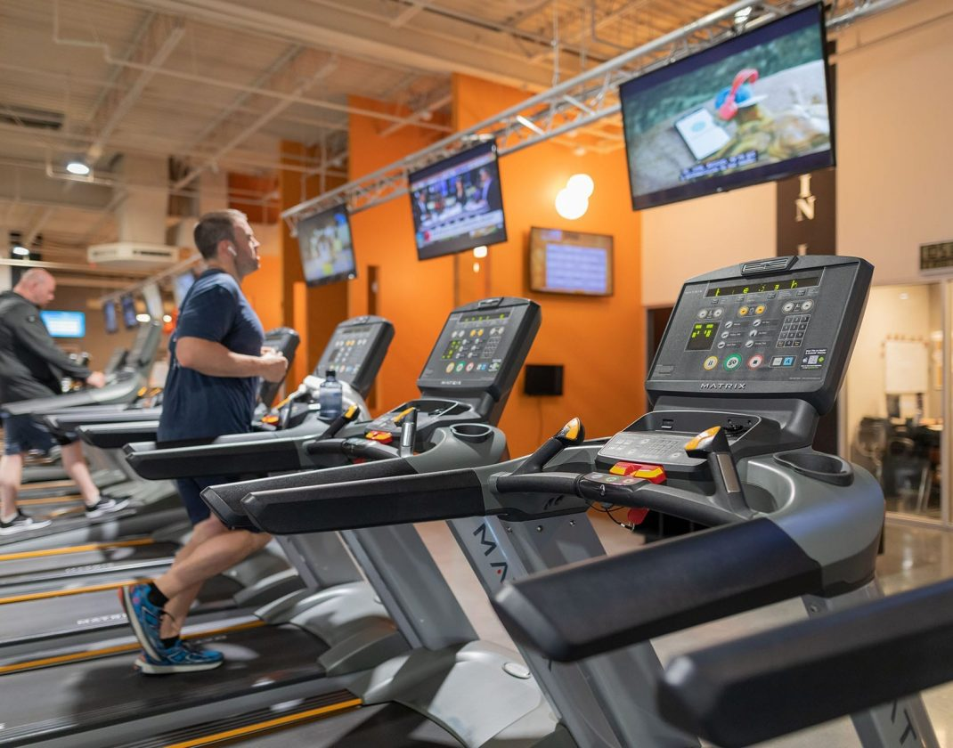 man running on treadmill in spacious gym