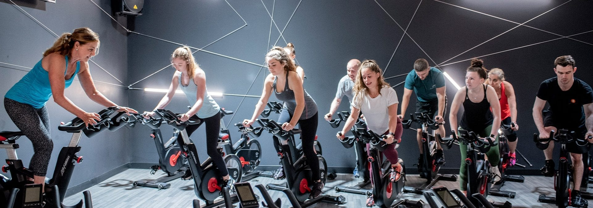 a large group of men and women in a modern and unique group cycle studio exercising in a gym near me
