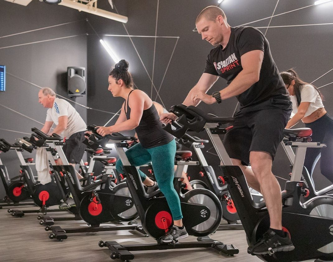 men and women exercising on spin machines in a spacious group spin studio with ambient lighting in the best gym in danvers