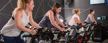 a group of people in a spacious and modern group spin studio exercising with a trainer in the best gym danvers