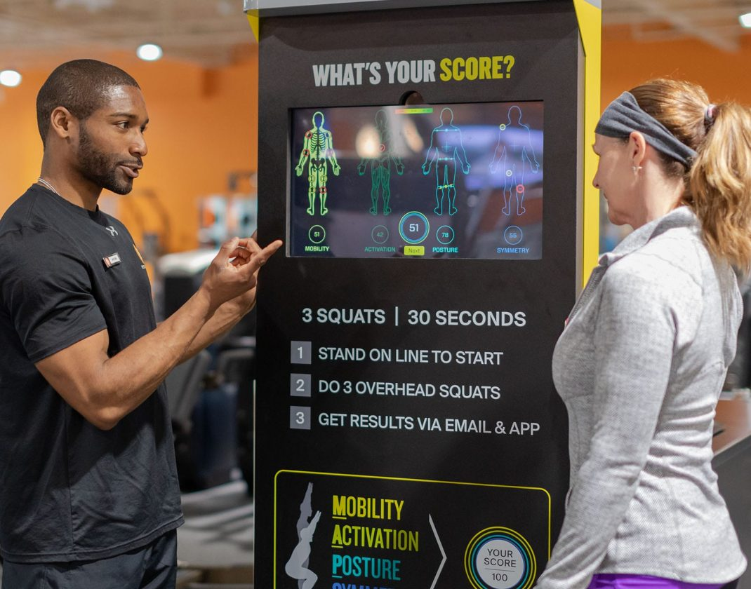 personal trainer showing results kiosk to gym member