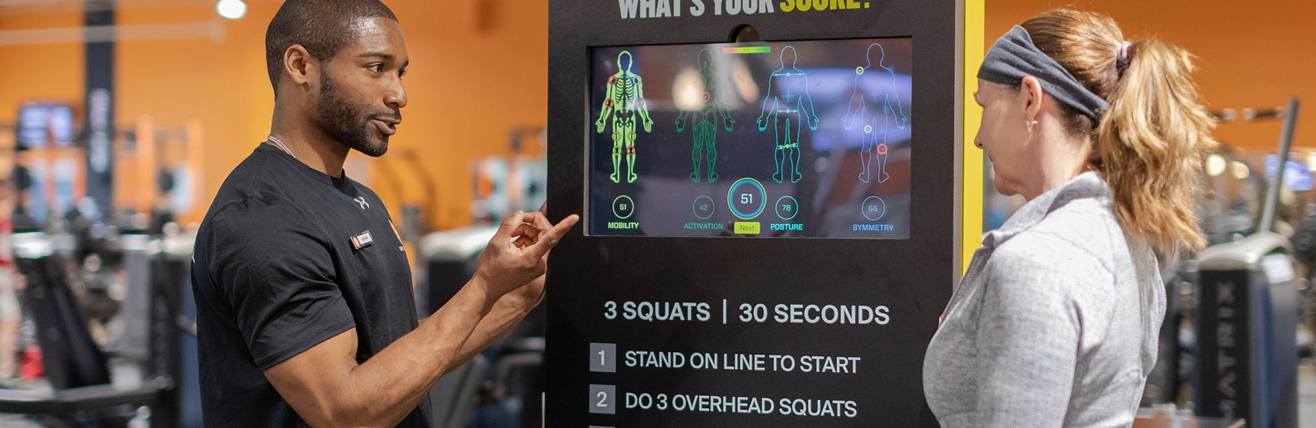 personal trainer showing gym member the results kiosk
