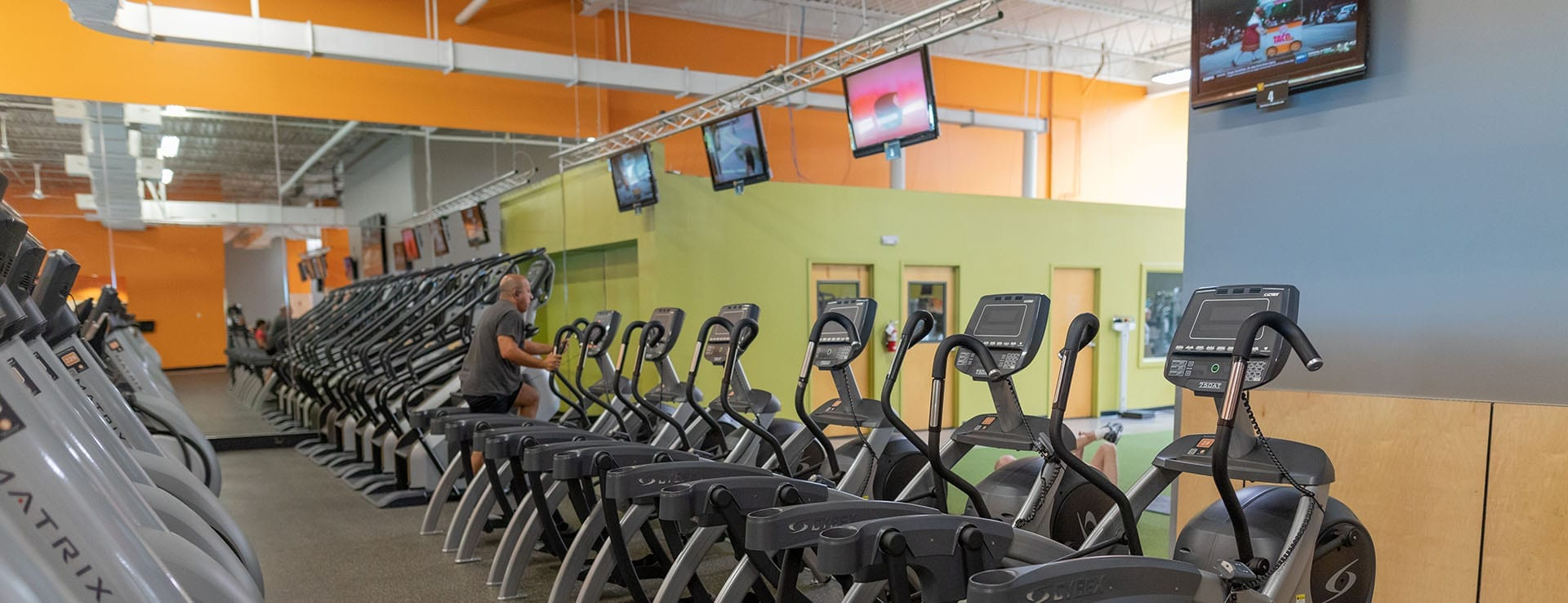 cardio equipment floor with tv monitors at modern gym