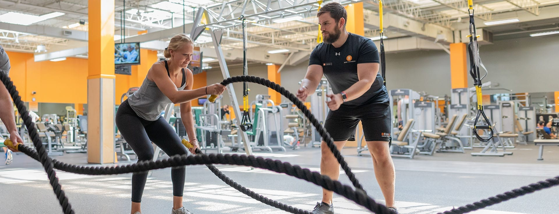 personal trainer guiding gym member in functional training exercises
